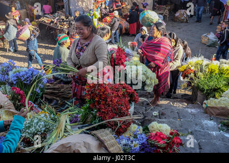 A mayan woman sells flowers in front of the church at the Sunday market in Chichicastenango, Guatemala. - Stock Photo