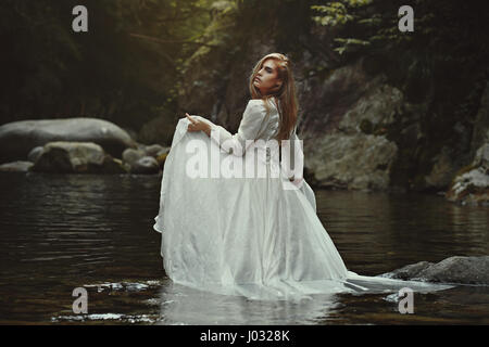Beautiful ethereal woman in mystical waters. Fantasy pond - Stock Photo