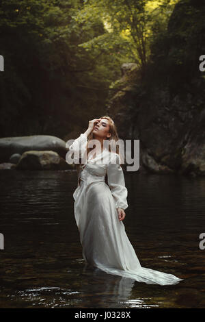 Young forest maiden in mystical waters. Dark woods - Stock Photo