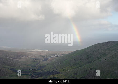 A Rainbow  overlooks La-Caleta in the north side of Lanzarote, Canary Islands. - Stock Photo