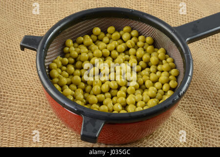 Canned sweet peas draining in strainer in bowl to lower salt content - Stock Photo