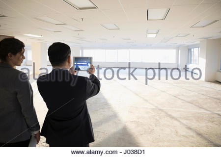 Businessman with digital tablet photographing empty, unfinished open plan office - Stock Photo