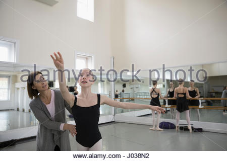 Female instructor guiding teenager ballet dancer practicing in dance studio - Stock Photo