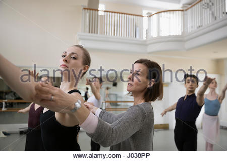 Instructor adjusting arms of female ballet dancer in dance studio - Stock Photo