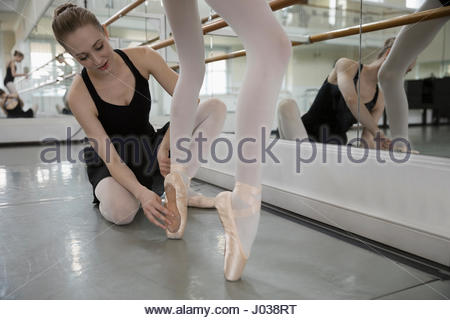 Female instructor adjusting foot of ballet dancer prodigy in dance studio - Stock Photo