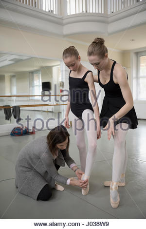 Female instructor and mentor adjusting foot of teenage ballet dancer prodigy in dance studio - Stock Photo