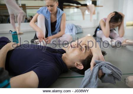 Tired male ballet dancer resting on floor in dance studio - Stock Photo