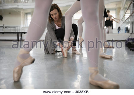 Female instructor adjusting foot of ballet dancer in dance studio - Stock Photo