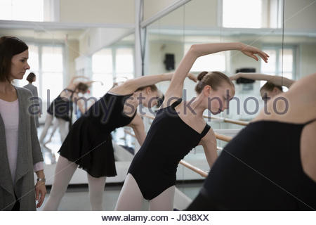 Female instructor watching ballet dancers practicing at barre in ballet studio - Stock Photo