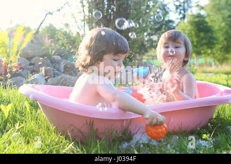 twins boy and girl in bath water outdoor - Stock Photo