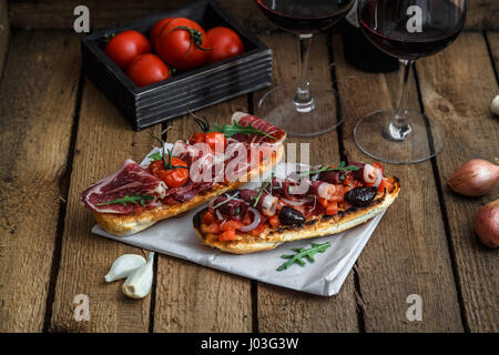 Wine appetizer set. Glass of red wine, brushettas with fresh tomato and jamon on over rustic grunge wooden background - Stock Photo