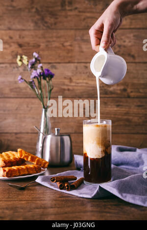 Women's hand with creamer pouring milk in glass with coffee. Cinnamon sticks, homemade cookies and bunch of wildflowers - Stock Photo