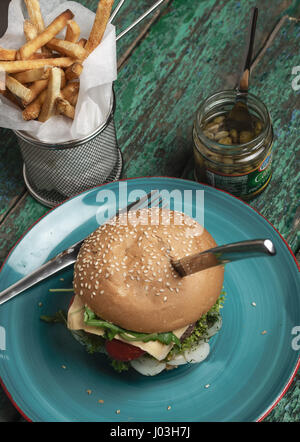 Cheese burger with french fries and capers on green grunge background - Stock Photo