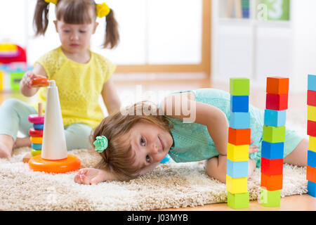Children playing with toys in kindergarten - Stock Photo