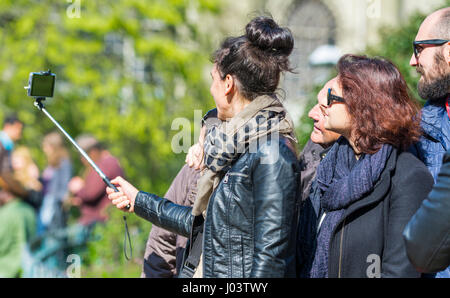 Tourists taking selfis photographs using a smartphone attached to a selfie stick. - Stock Photo