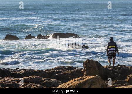 Young man standing on a rocks of Atlantic Ocean shore in Nevogilde civil Parish of Porto city, second largest city - Stock Photo