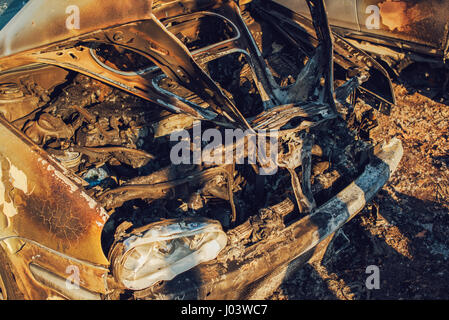 Burned vehicle on parking lot, abandoned stolen car - Stock Photo