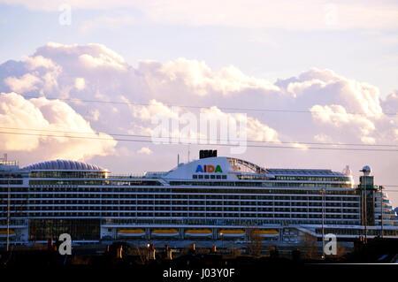 The Aida cruise ship liner with a towering Cumulonimbus cloud in the background - Stock Photo