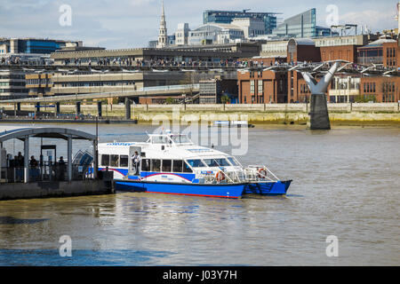 Blue and white Catamaran Thames Clipper boat forming part of the river bus service at Bankside pier by the Millennium - Stock Photo