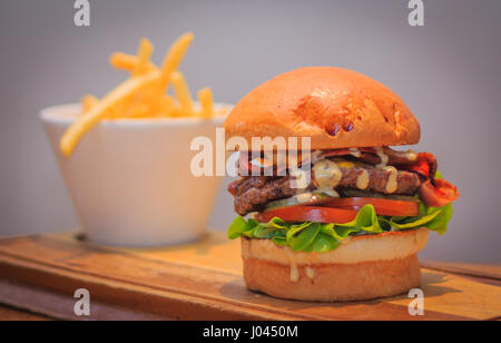 American Beef Brisket burger with special sauce, oak lettuce, tomato, pickle, bacon, cheese, milk bun and french - Stock Photo