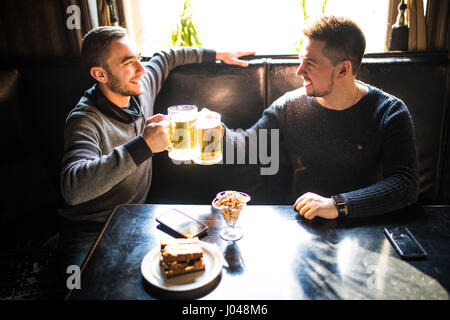 two young man sitting in pub, eating and drinking beer at pub. Friends. - Stock Photo