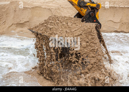 The bucket of sand of a mechanical shovel in action on the beach, at Capbreton (Landes - Aquitaine - France). - Stock Photo