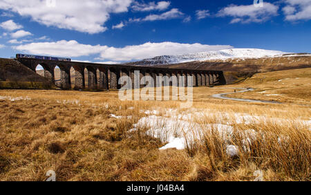 Ribblehead, England, UK - April 1, 2013: A Northern Rail Class 158 diesel passenger train passes the snow-covered - Stock Photo