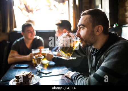 Man drink beer in front of to discussing drinking friends in pub. - Stock Photo