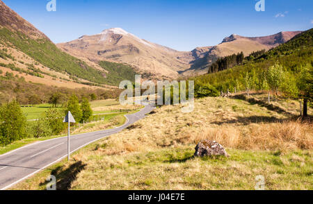 A small country road winds through pastures and woodland in the valley floor of Glen Nevis under the mountains of - Stock Photo