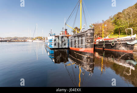 Crinan, Scotland, UK - June 3, 2011: The Vital Spark Clyde Puffer and other boats sit docked in the basin of the - Stock Photo