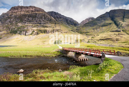 A small bridge crosses the River Coe to Achnambeithach Cottage nestled under the sheer mountains of Glen Coe in the West Highlands of Scotland.