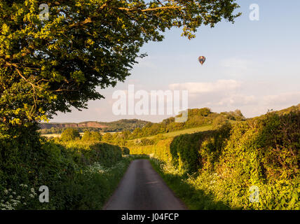 A hot air balloon floats over the fields and lanes of the rolling farmland landscape of England's Mendip Hills in - Stock Photo