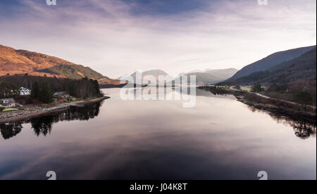 The mountains of Glen Coe reflected in Loch Linnhe sea loch, viewed from the Ballchulish Bridge in the West Highlands - Stock Photo