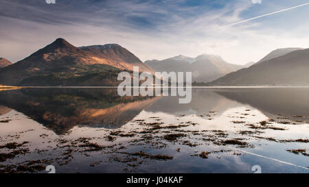 The mountains of Glen Coe are reflected in Loch Leven sea loch in the West Highlands of Scotland. - Stock Photo