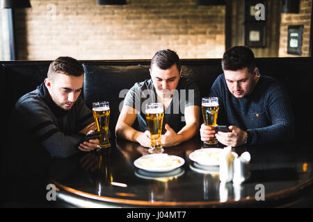 Three young men in casual clothes are talking, using a smart phone and drinking beer while sitting in pub - Stock Photo