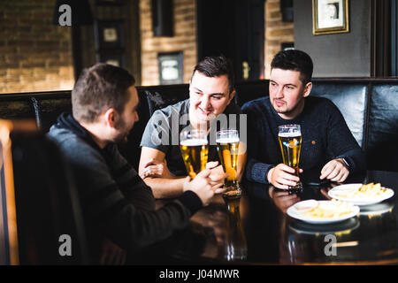 Three young men in casual clothes are talking, eating chips and drinking beer while sitting in pub, close-up - Stock Photo