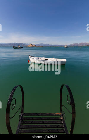 Pier Steps, Traditional Fishing Boats and Bourtzi Fortress in the distant background in Nafplion, Greece- portrait - Stock Photo