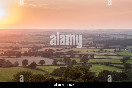 The sun sets over a patchwork of pasture fields, crops and woodland in the Blackmore Vale farming district of North - Stock Photo