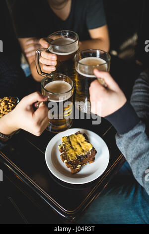 people, leisure and drinks concept - close up of male hands clinking beer glasses and pretzels at bar or pub - Stock Photo