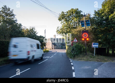Shaftesbury, England, UK - July 28, 2012: Traffic rushes through Melbury Abbas village in rural north Dorset, activating - Stock Photo