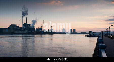 London, England, UK - March 7, 2010: Sunrise silhouettes steam rising from the Tate & Lyle sugar refinery on the - Stock Photo