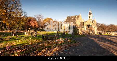 London, England, UK - November 11, 2012: Trees display autumn colours and drop leaves on graves around the chapel - Stock Photo