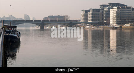 London, England, UK - March 5, 2013: A freight train crosses the River Thames between Battersea and Chelsea's Imperial - Stock Photo