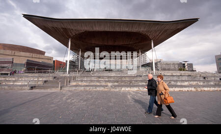 Cardiff, Wales - March 17, 2013: A couple walk past the Welsh Assembly Parliament building in Cardiff Bay. - Stock Photo