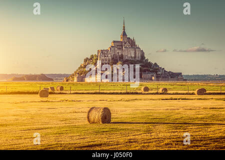 Beautiful view of famous historic Le Mont Saint-Michel in golden evening light at sunset in summer with hay bales on fields, Normandy, France