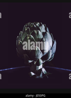 Artichoke on black background. Close up. Rustic style. - Stock Photo