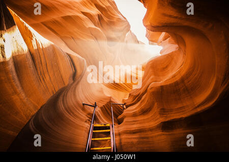 Beautiful view of amazing sandstone formations with a ladder leading toward a magic light beam in famous Antelope - Stock Photo