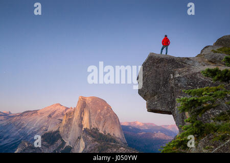 A fearless hiker is standing on an overhanging rock enjoying the view towards famous Half Dome at Glacier Point - Stock Photo