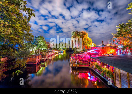 Panoramic view of young people partying in an open-air outdoor club at famous Flutgraben water canal on a beautiful - Stock Photo