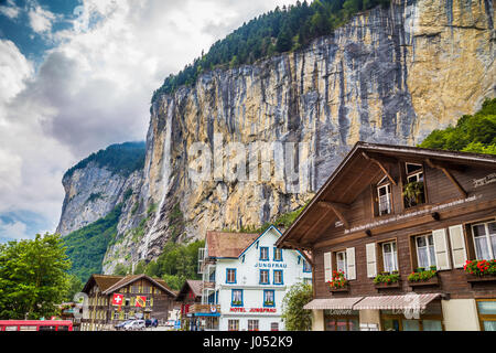 Beautiful view of the historic town of Lauterbrunnen with famous Staubbach Falls in the background on a sunny day - Stock Photo